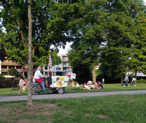 An ice cream man on an electric bike.